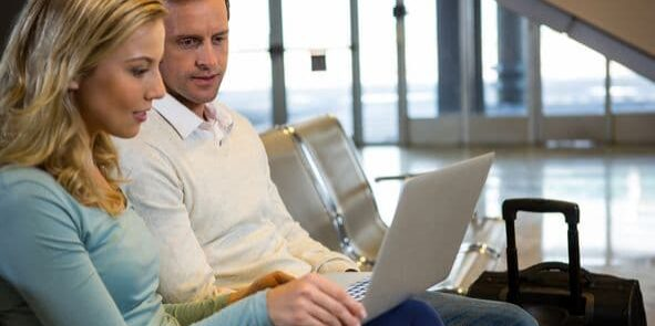 Couple sitting with laptop in the waiting area at airport terminal